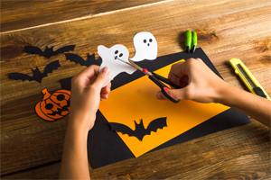 Photograph of a child cutting out paper ghosts